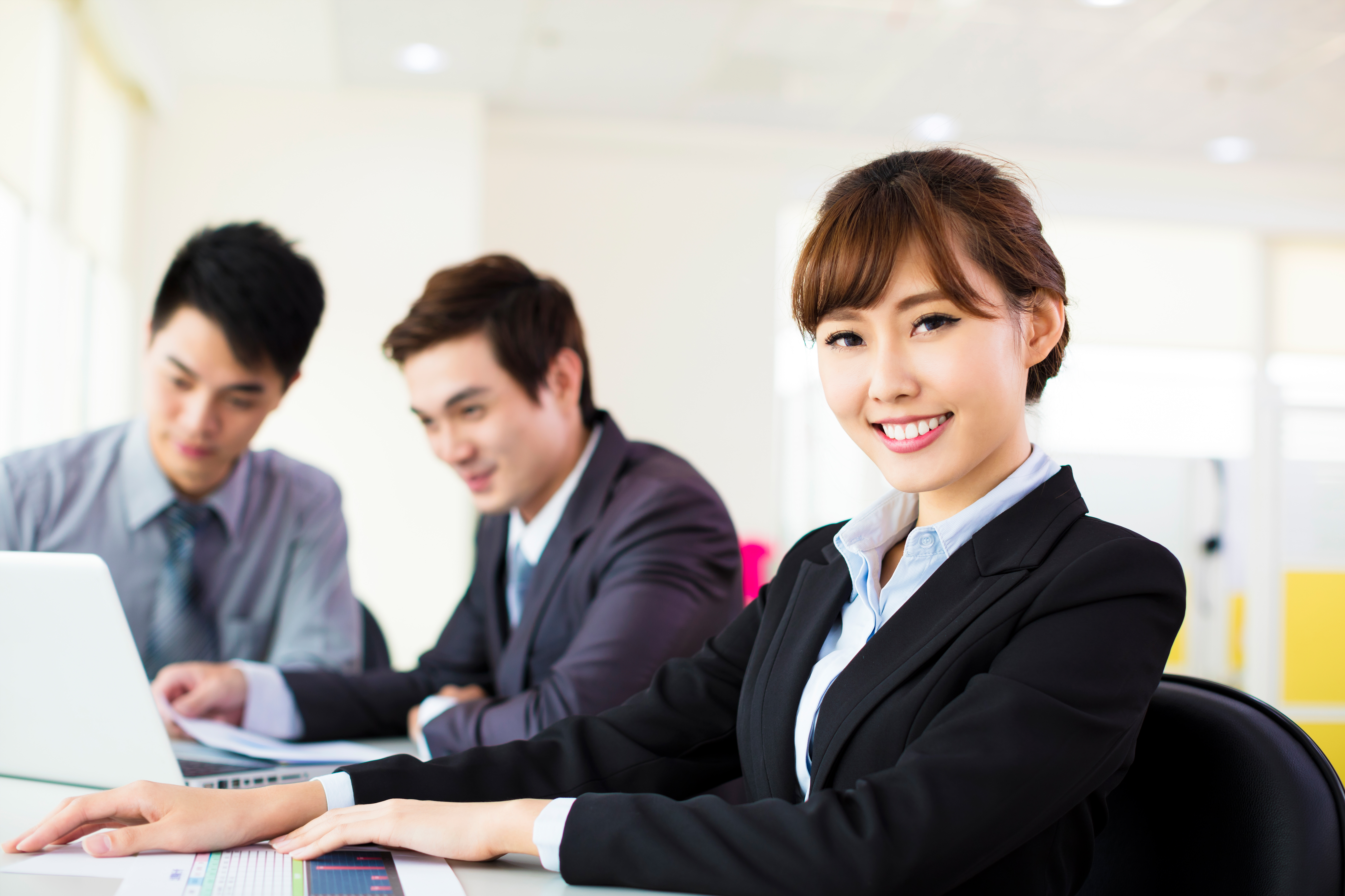 1 female working adult and 2 male colleagues in office