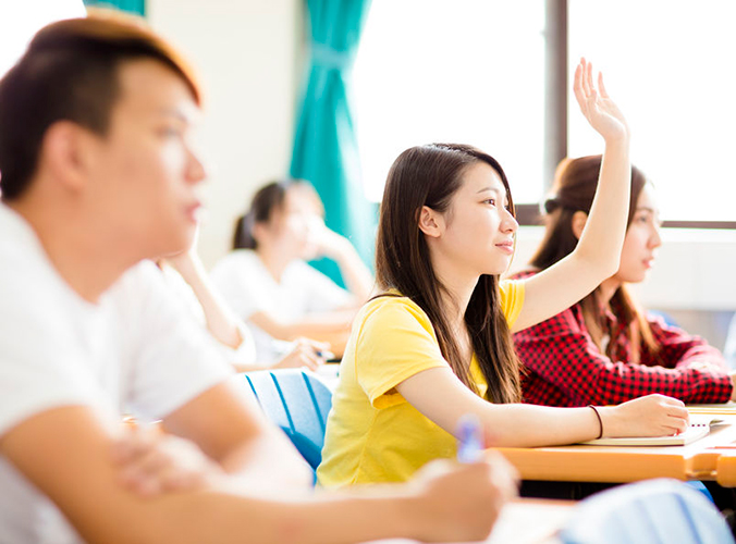 a female student raising her hand in class
