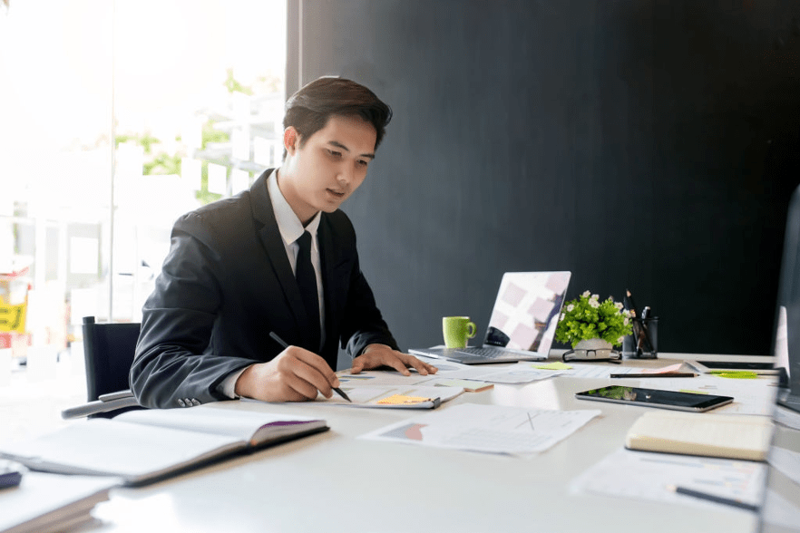 an asian writing in office