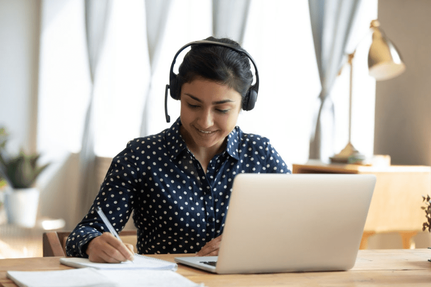 an female Indian student writing during online class