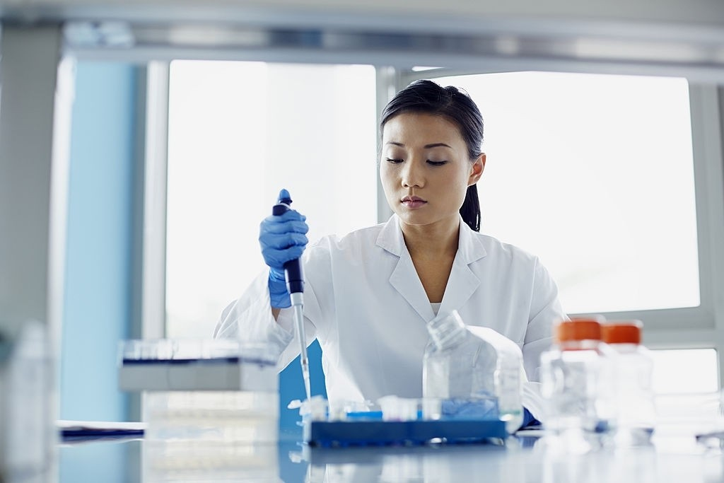 Female scientist using pipette in modern research laboratory
