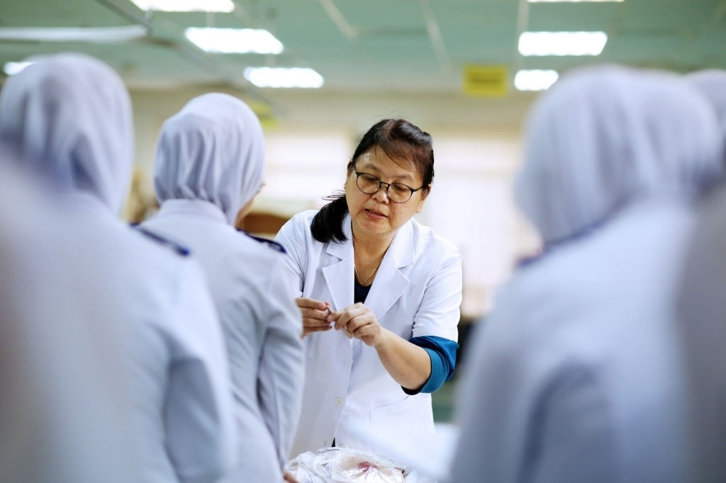 A nursing tutor is guiding a group of Muslim student nurses in the hospital with medical advise.