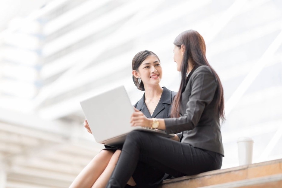 2 working office ladies sitting and meeting outdoor