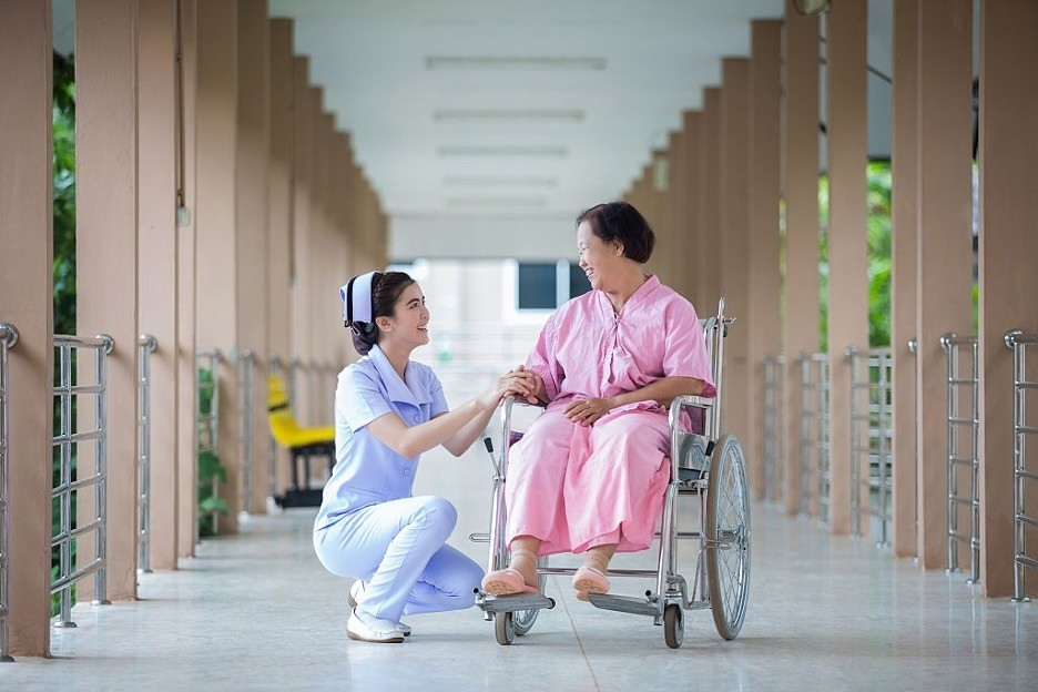 a nurse is smiling to female wheelchair patient