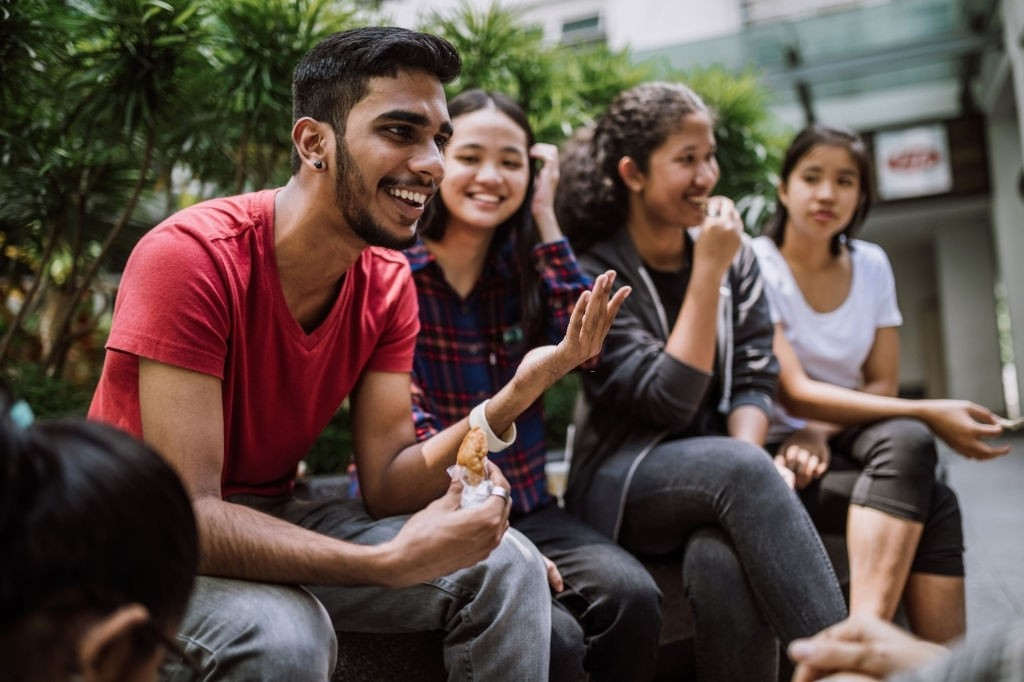 Multi Ethnic Group Of Students Joking And Getting To Know Each Other Better On Lunch Break in University Yard