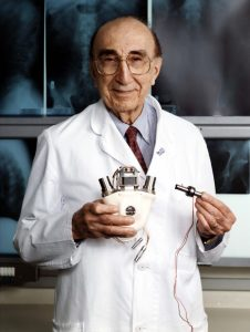 Dr. Michael DeBakey holding an artificial heart.