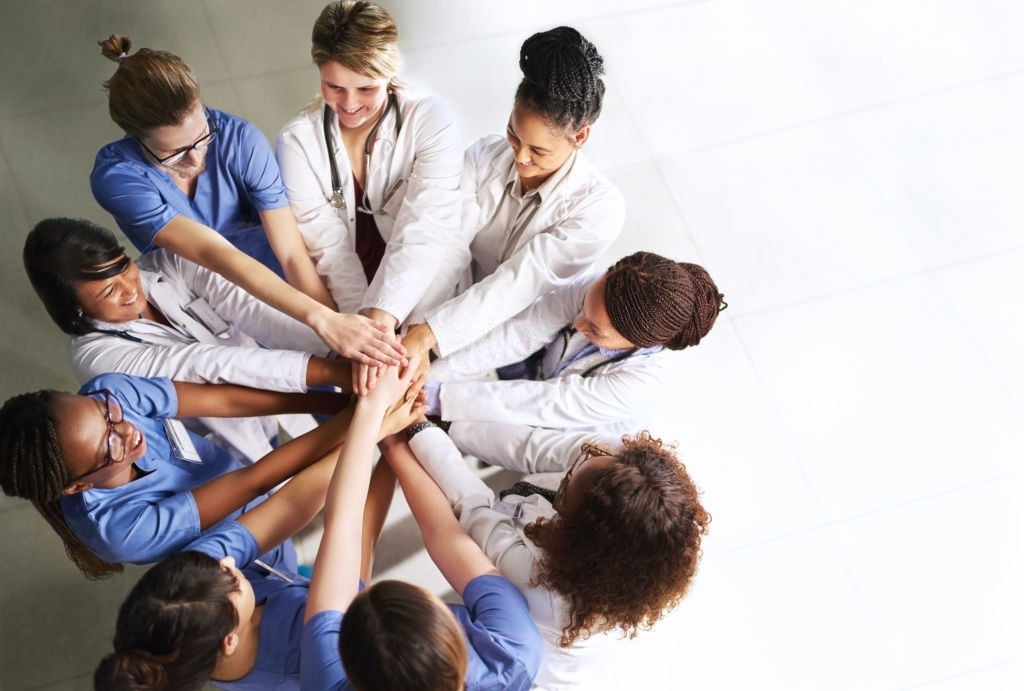 High angle shot of a group of medical practitioners joining their hands together in a huddle