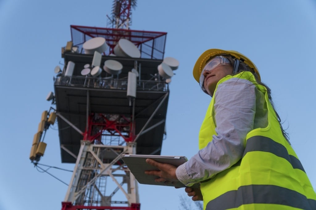 Engineer working on the field near a Telecomunications tower