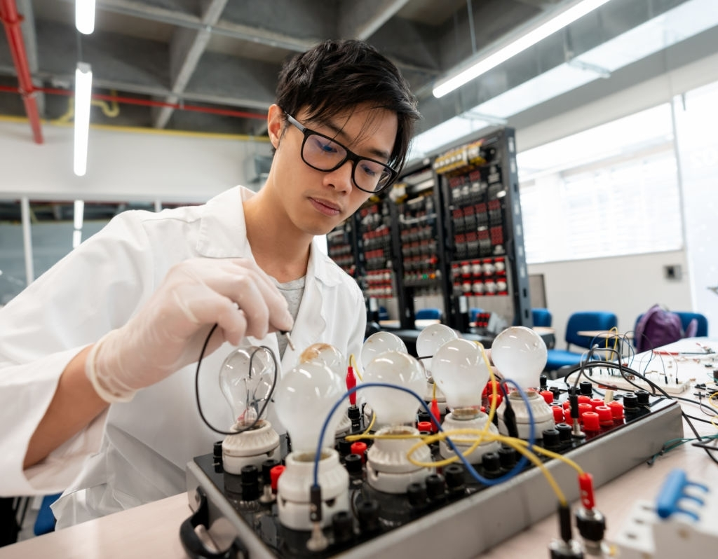 Asian student at electronics laboratory experimenting looking focused