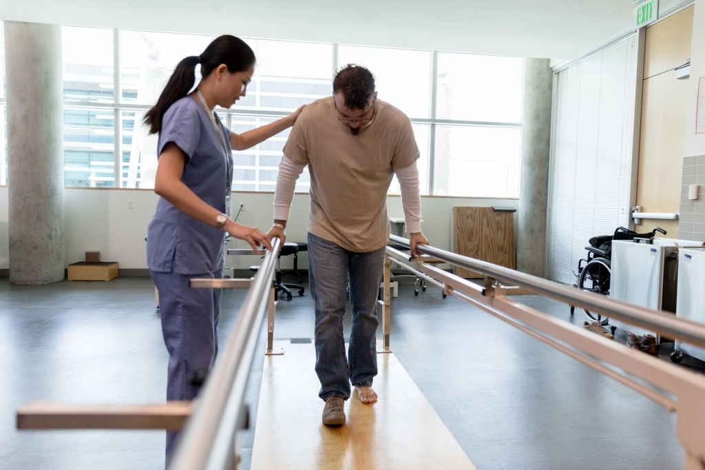 Male patient takes first steps using orthopedic parallel bars