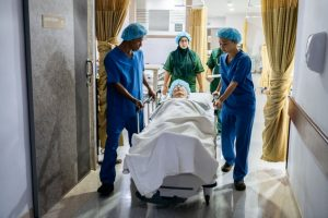 Asian doctors with gurney on way to operating theatre, senior man lying on bed