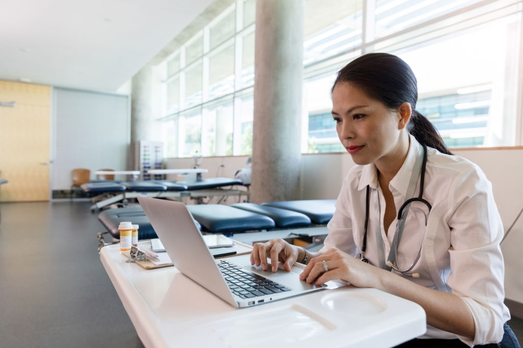 Mid adult female doctor uses laptop in physical therapy room